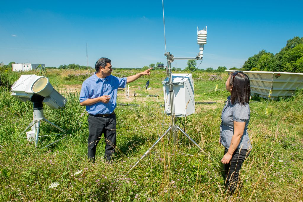 Argonne National Laboratory researchers V. Rao Kotamarthi, left, and Yan Feng take climate data from instruments on the Argonne campus. They are both part of the cloud-aerosols SFA.