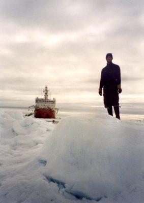 During the SHEBA campaign, in 1998, Matthew Shupe poses atop an ice feature. The Canadian icebreaker Des Groseilliers is in the background. Photo courtesy of Shupe.