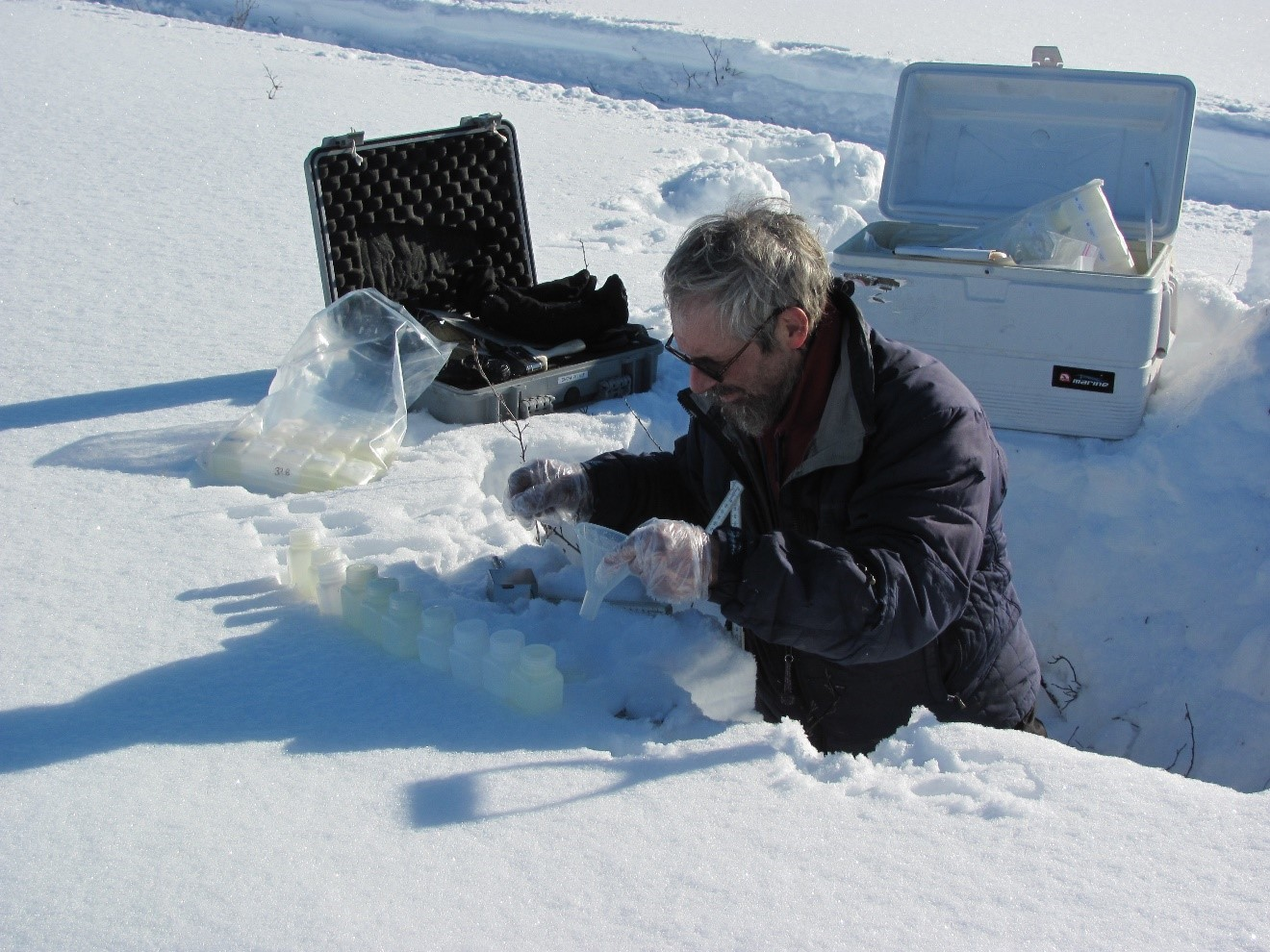 Standing in a field-site pit, Matthew Sturm collects snow samples. Different types influence the albedo of snow cover.
