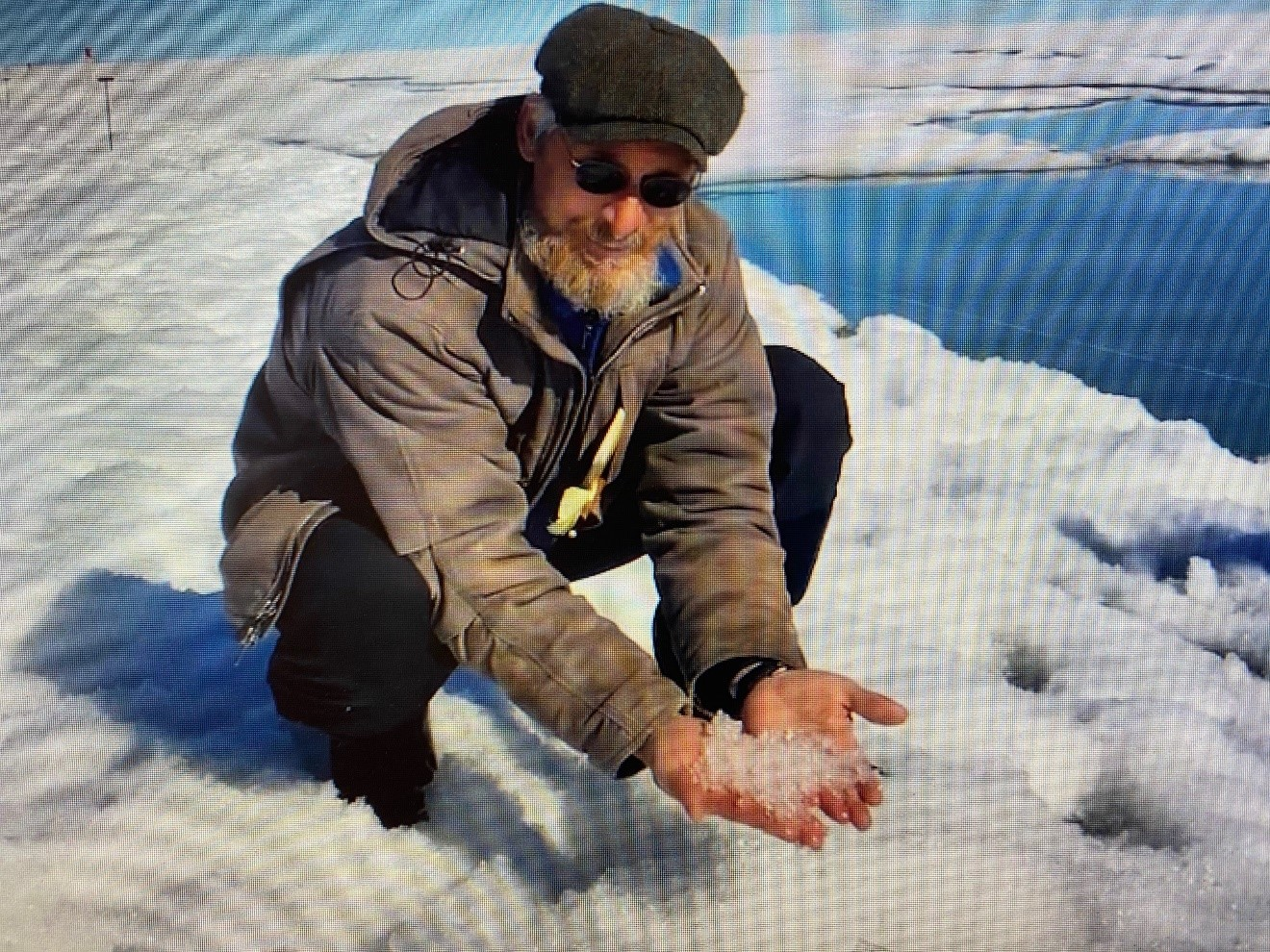During a 2019 snow-sampling excursion in the North Slope of Alaska, Matthew Sturm scoops up icy snow near a springtime melt pond. YouTube screengrab from a video by the Geophysical Institute, University of Alaska Fairbanks.