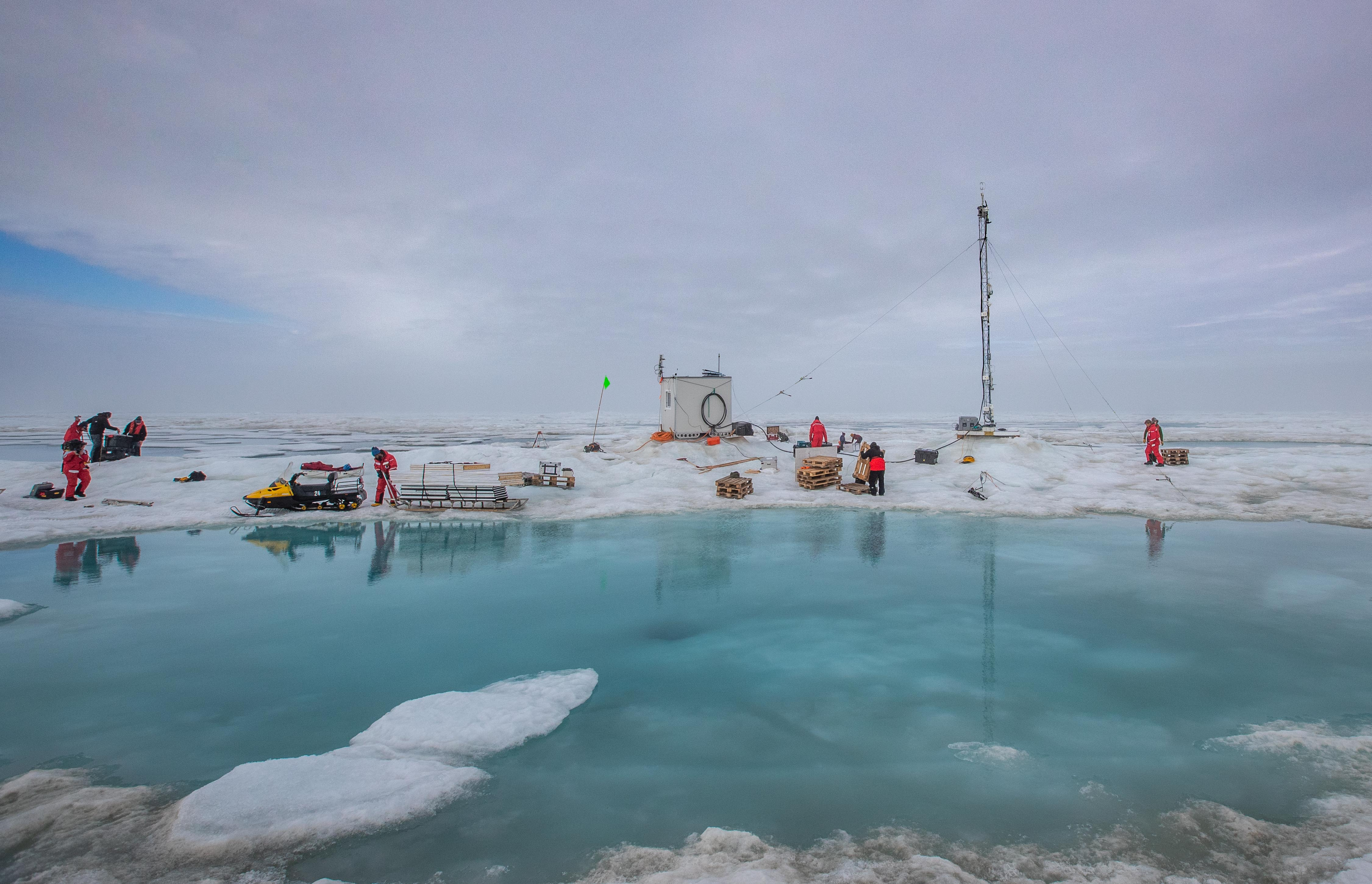 MOSAiC team members pack up instruments within the Met City research station, which is situated directly next to a melt pond.