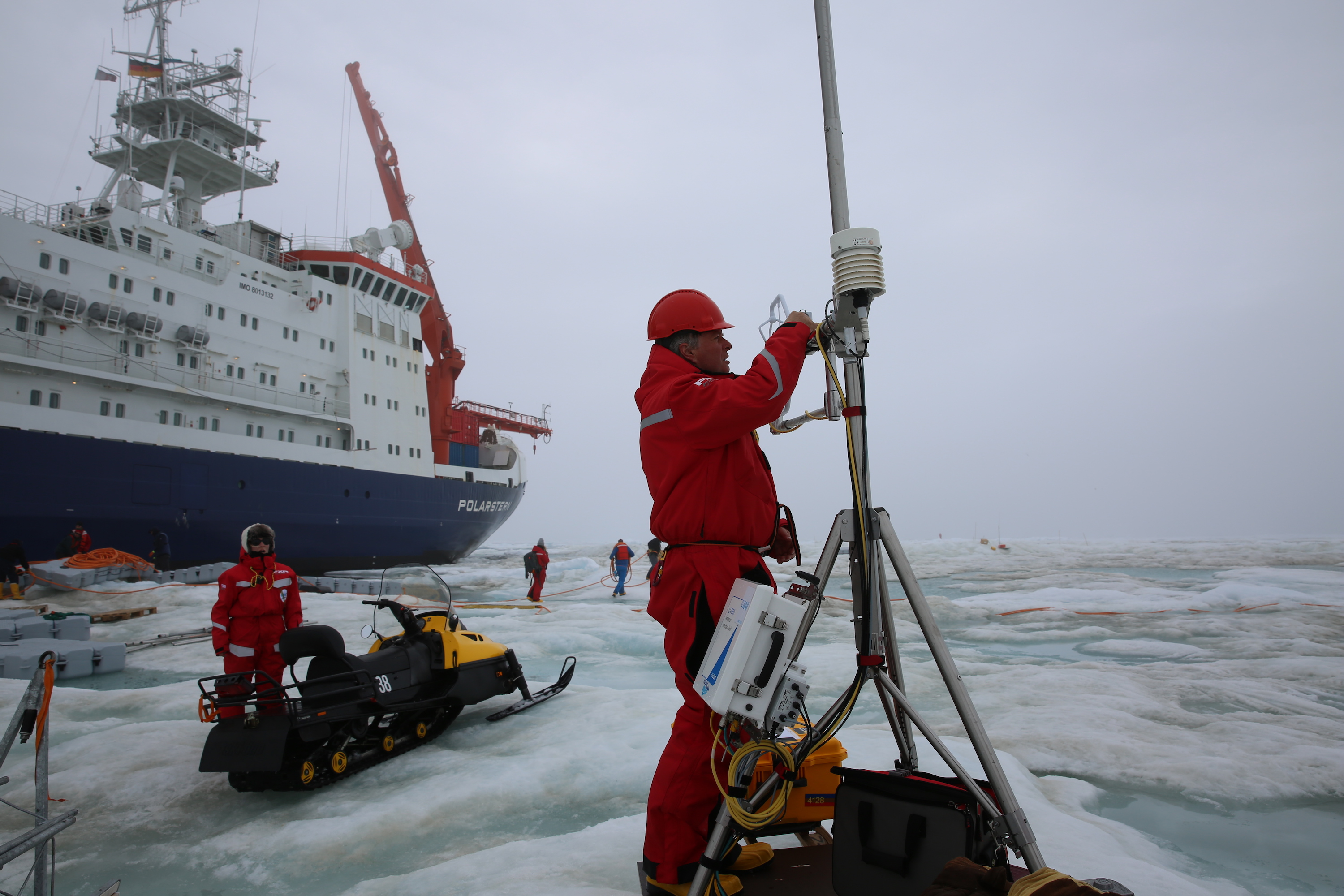 A MOSAiC team member removes sensors from an instrument before bringing it back onto the icebreaker R/V Polarstern. In the background, people recover the orange power cables, which supplied the central observatory with electricity.