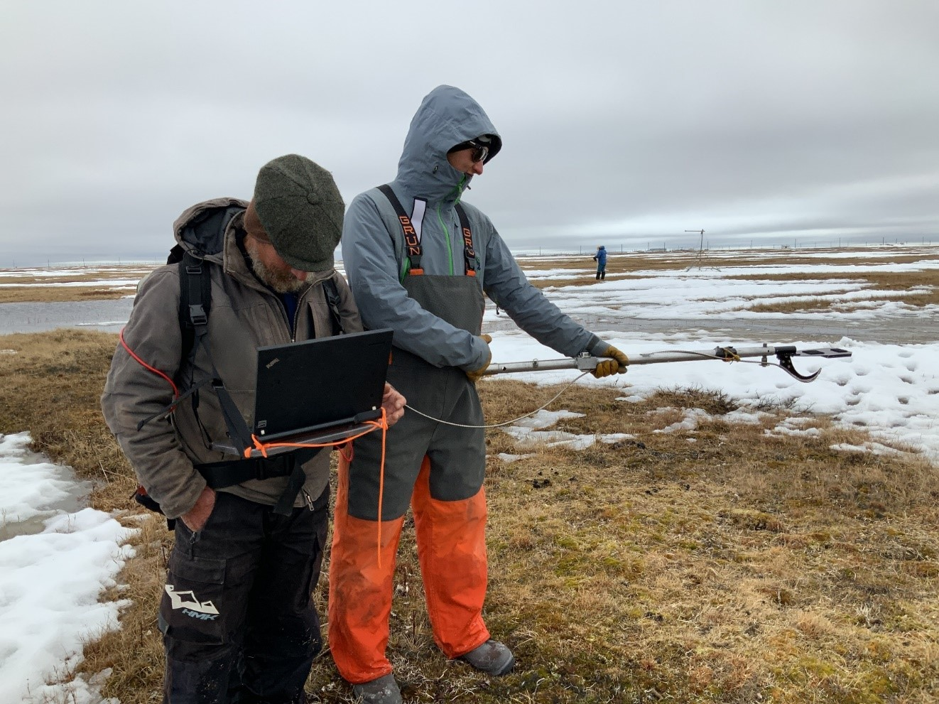 Sturm, left, studies a computer readout during SALVO work in the spring of 2019. Dark patches of tundra emerge to soak up more heat, decreasing the albedo of the landscape.