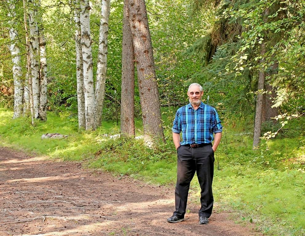 "In a rare snowless moment, Sturm pauses on a forested path in Fairbanks. He calls summer in Alaska ""the unusual season."""